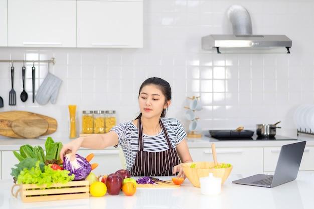 La femme des médias sociaux cuisine dans la cuisine de la maison et diffuse en direct ou enregistre des vidéos sur les médias sociaux dans sa maison.