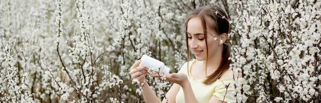 Femme avec des médicaments dans les mains lutte contre les allergies printanières en plein air - portrait d'une femme allergique entourée de fleurs de saison