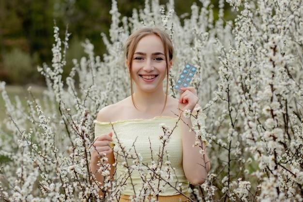 Femme avec des médicaments dans les mains lutte contre les allergies printanières en plein air - portrait d'une femme allergique entourée de fleurs de saison.