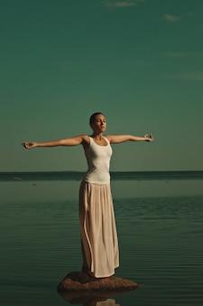 Femme méditant dans une pose de yoga sur la plage au coucher du soleil