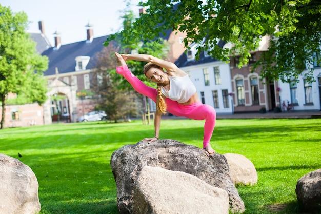Femme méditant et faisant du yoga asana exercisers dans le parc