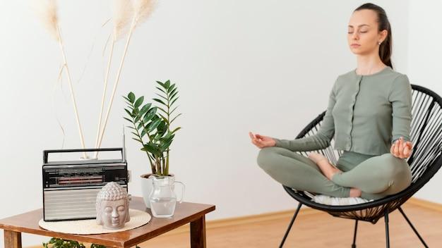 Femme méditant à la maison sur une chaise