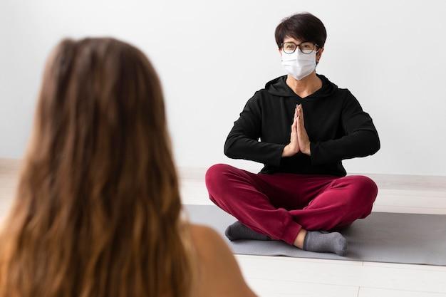 Femme méditant avec un masque facial sur
