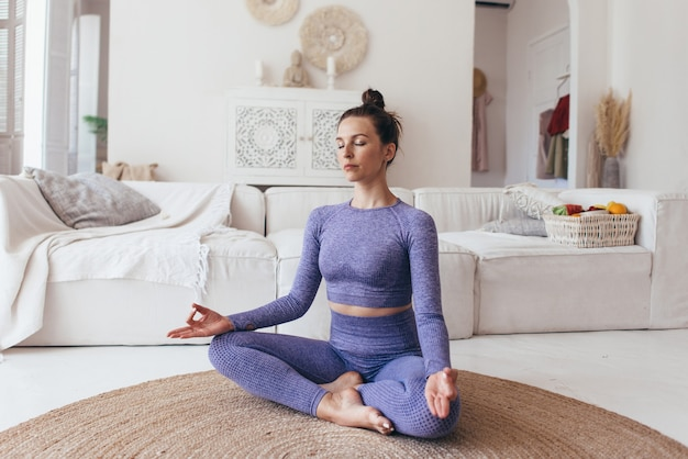 Femme méditant en position de yoga lotus, pratiquant le yoga.