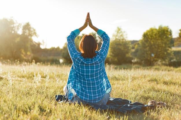 Femme méditant, pratiquant le yoga dans la nature