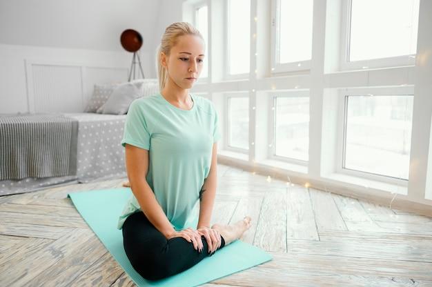 Femme méditant sur tapis