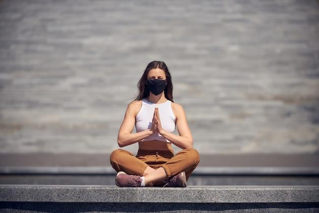 Une femme médite dans un lieu public vide dans un masque noir. épidémie de photo concept coronavirus