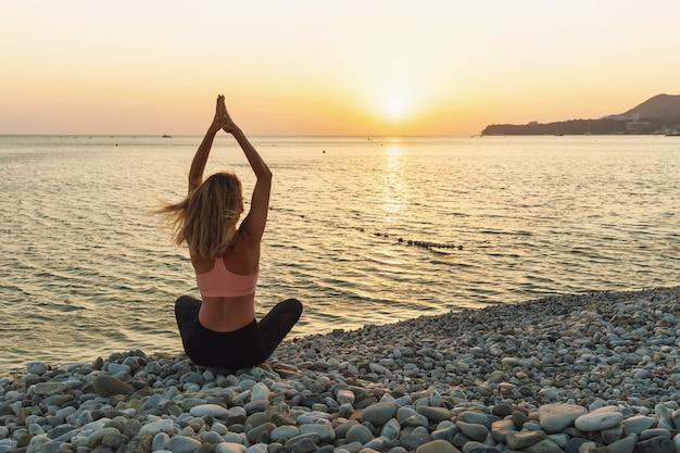 Une femme médite avec ses mains levées assise dans une pose de lotus sur un bord de mer de galets