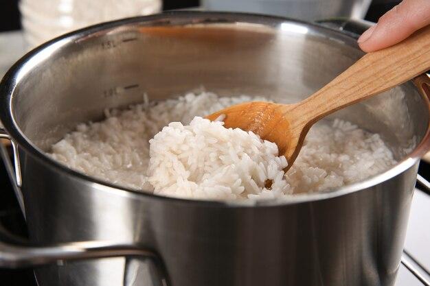 Femme mélangeant du riz dans une casserole avec une cuillère