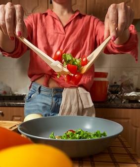 Femme mélangeant une salade saine dans la cuisine