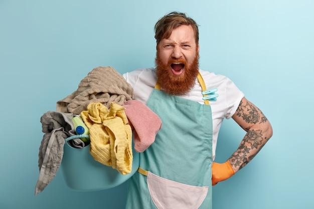 La femme de ménage agacée garde la main sur la taille, crie avec colère, porte un t-shirt et un tablier décontractés
