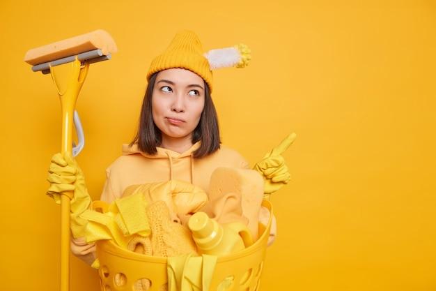 Une femme de ménage asiatique sérieuse et sans émotion en tenue décontractée indique à l'espace de copie vierge tient la vadrouille fait le ménage fait régulièrement des promotions pour le produit de nettoyage isolé sur fond jaune