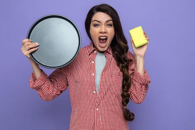 Femme de ménage assez agacée tenant une assiette et une éponge