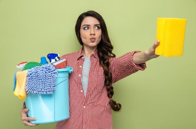 Femme de ménage assez caucasienne confiante tenant un équipement de nettoyage et une éponge et regardant de côté
