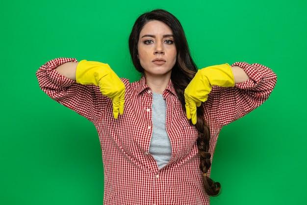 Femme de ménage assez confiante avec des gants en caoutchouc pointant vers le bas et regardant vers l'avant