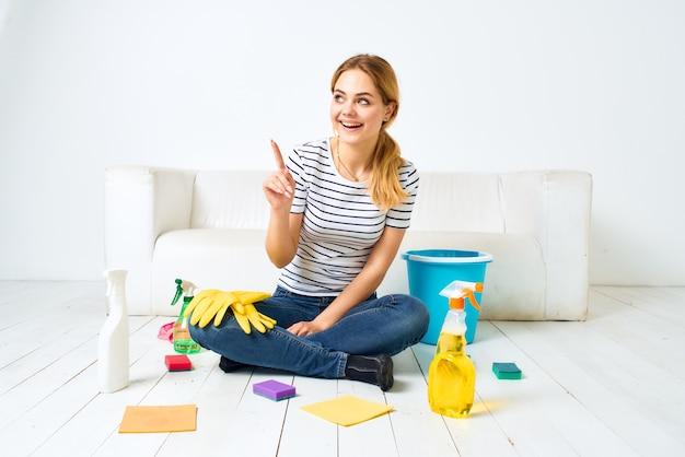 Femme de ménage assise sur le sol fournitures de nettoyage nettoyage intérieur de la maison