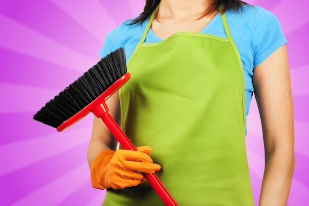 Femme de ménage avec un balai travaux ménagers