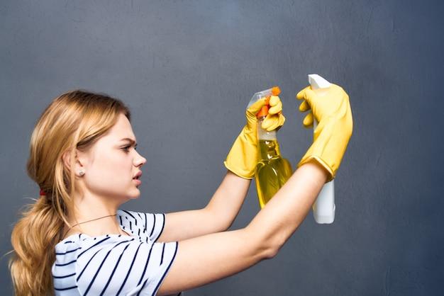 Femme de ménage en caoutchouc jaune gants détergents soins à domicile gris.