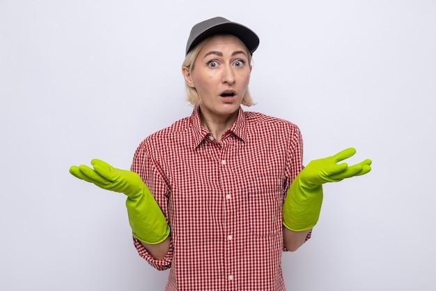 Femme de ménage en chemise à carreaux et casquette portant des gants en caoutchouc à la confusion écartant les bras sur les côtés