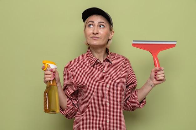 Femme de ménage en chemise à carreaux et casquette tenant une bouteille de produits de nettoyage et une vadrouille en levant perplexe en pensant positivement