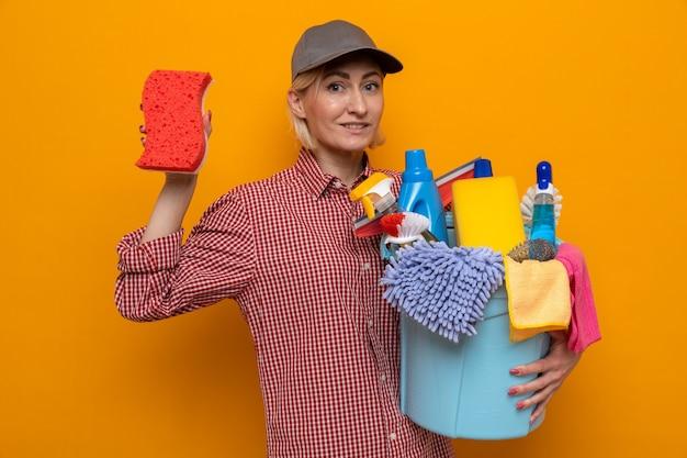 Femme de ménage en chemise à carreaux et casquette tenant une éponge et un seau avec des outils de nettoyage regardant la caméra souriante confiante prête pour le nettoyage debout sur fond orange