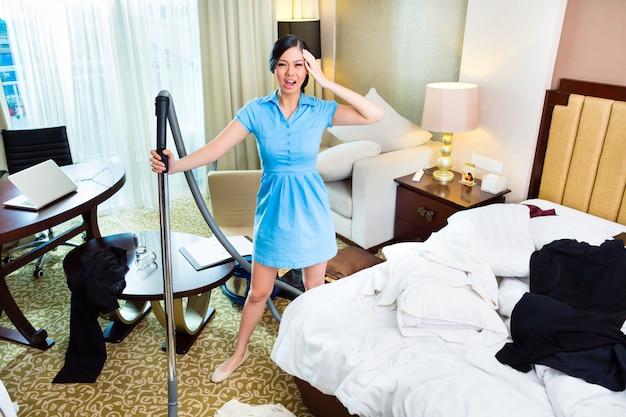 Femme de ménage dans une chambre d'hôtel asiatique