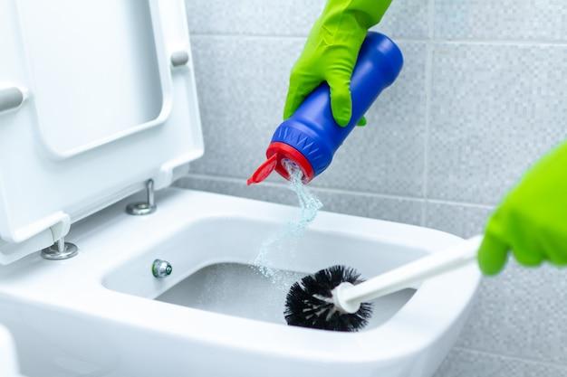Femme de ménage dans des gants en caoutchouc pour laver et désinfecter les toilettes à l'aide de produits de nettoyage et d'une brosse à récurer. tâches ménagères et service de nettoyage