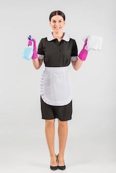 Femme de ménage avec détergent et plumeau souriant