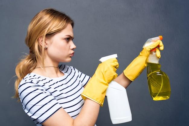 Femme de ménage émotionnelle avec un détergent dans les mains du service de soins à domicile rendu gris intérieur.