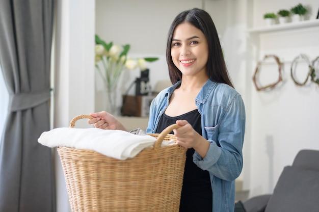 Une femme de ménage heureuse porte un seau pour la lessive dans la maison.