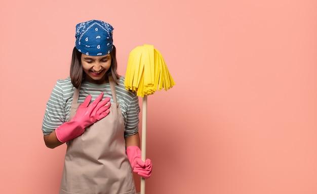 Femme de ménage jeune femme riant à haute voix à une blague hilarante, se sentir heureux et joyeux, s'amuser