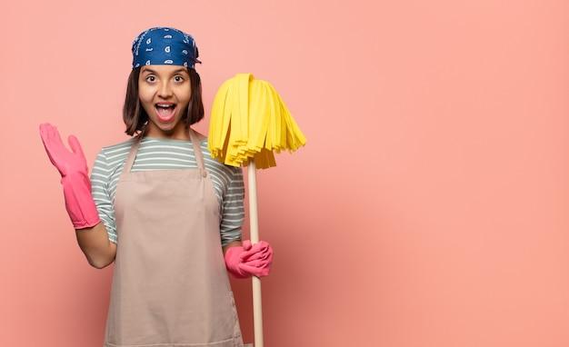 Femme de ménage de jeune femme se sentant heureuse, excitée, surprise ou choquée, souriante et étonnée de quelque chose d'incroyable
