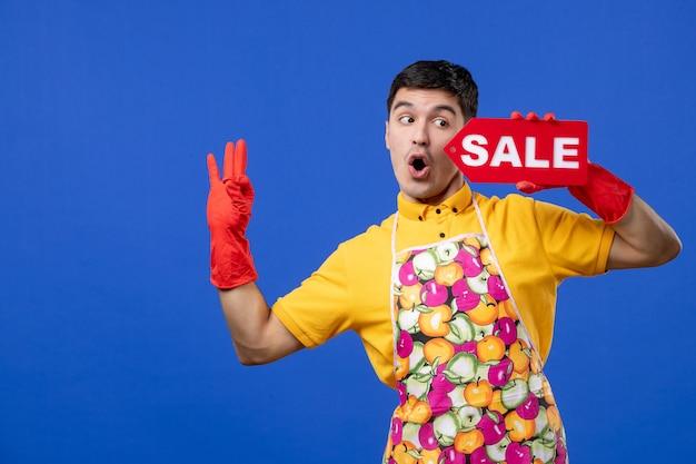 Femme de ménage mâle vue de face avec des gants de vidange rouges tenant une pancarte de vente faisant une pancarte okey sur un espace bleu
