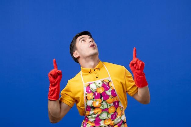 Femme de ménage mâle vue de face en tablier pointant avec le doigt vers le haut