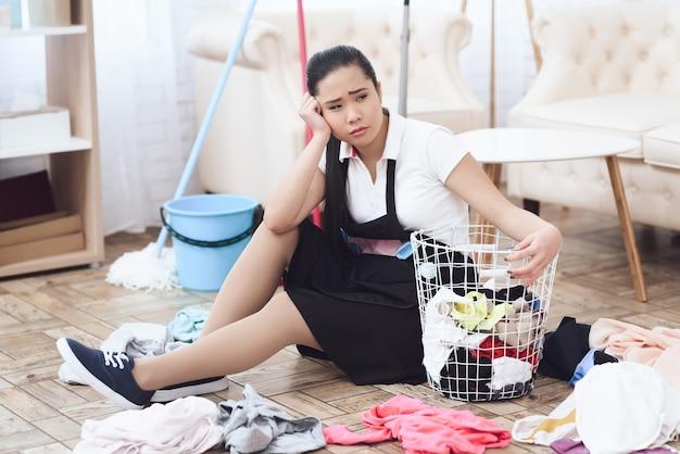 Femme de ménage malheureuse avec panier à linge, travail acharné.