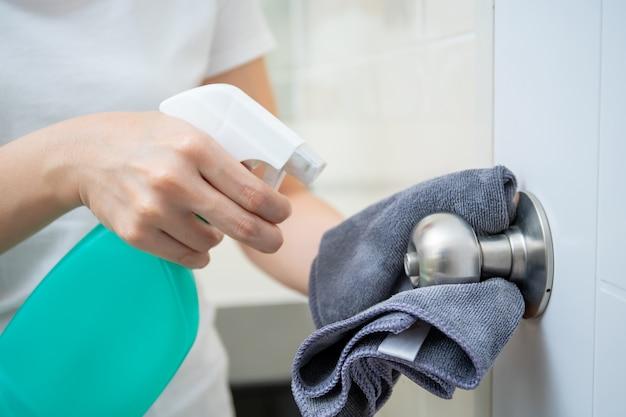 Femme de ménage nettoyant un bouton de porte en acier inoxydable sale dans les toilettes.