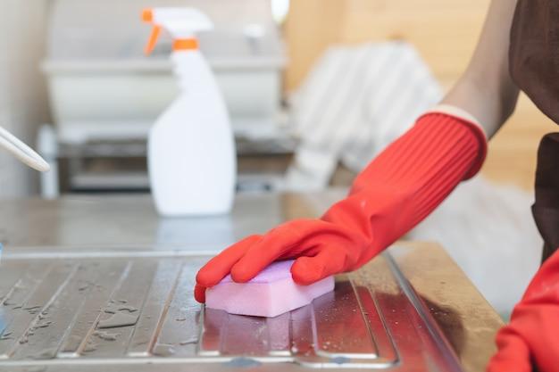 Femme de ménage nettoyant évier dans la cuisine avec éponge et nettoyant.