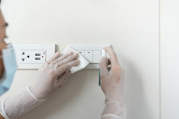 Femme de ménage nettoyant un interrupteur avec une lingette humide, un spray d'alcool. concept de surface de désinfection