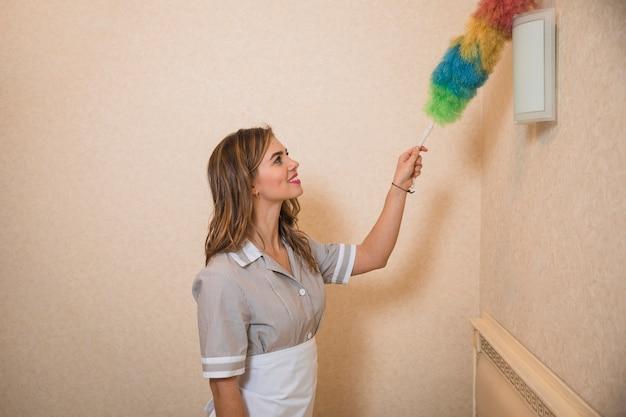 Femme de ménage occupée à nettoyer la lampe murale avec un plumeau coloré