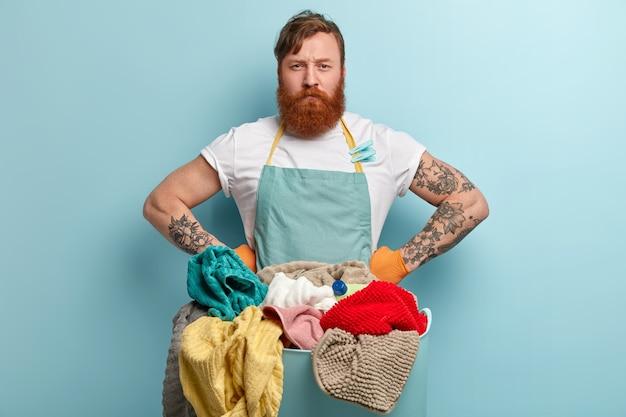 Une femme de ménage occupée sérieuse garde les mains sur la taille regarde directement la caméra avec une expression faciale mécontente