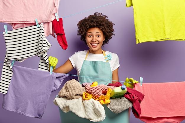 Femme de ménage à la peau sombre souriante accroche des vêtements propres avec des pinces à linge sur la ligne à laver