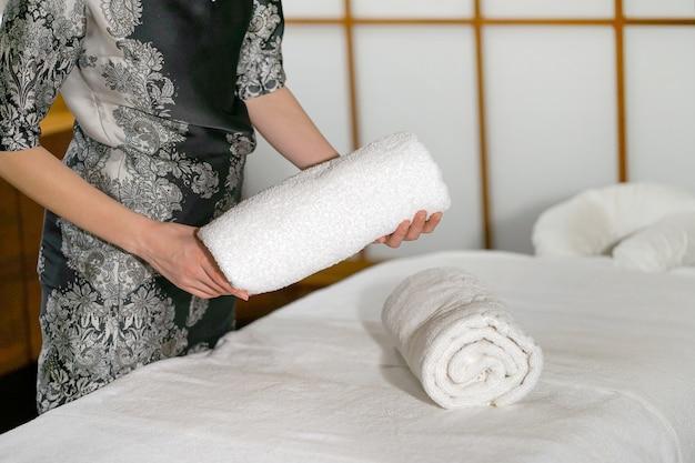Une femme de ménage plie une serviette sur un lit de massage.