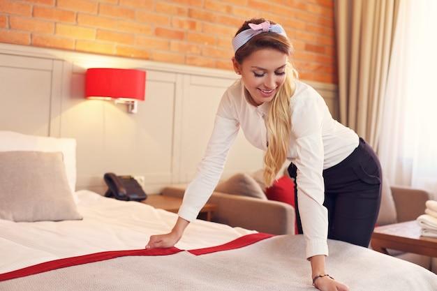 Femme de ménage préparant la chambre d'hôtel