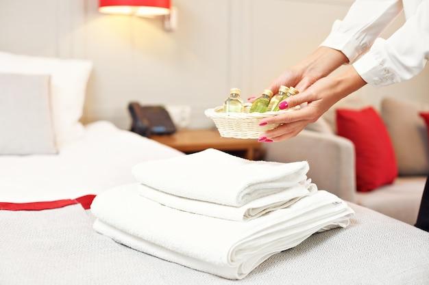 Femme de ménage préparant des cosmétiques dans une chambre d'hôtel
