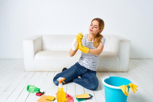 Femme de ménage près du canapé chiffons détergents éponges gants de protection