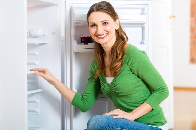 Femme de ménage avec réfrigérateur