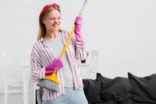 Femme de ménage s'amusant avec une brosse