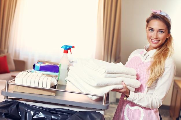 Femme de ménage avec des serviettes propres dans la chambre d'hôtel