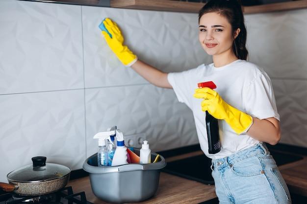 Femme de ménage souriante dans la cuisine de nettoyage de gants jaunes de protection avec des détergents