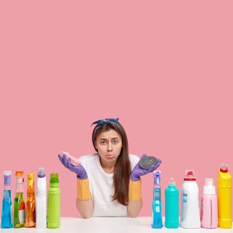 Une femme de ménage surmenée insatisfaite porte un sac à main à la lèvre inférieure en signe de mécontentement, tient un chiffon et une éponge dans les mains, porte des gants en caoutchouc